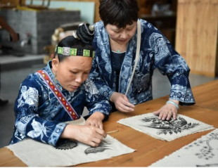 Miao women are painting batik patterns by hand